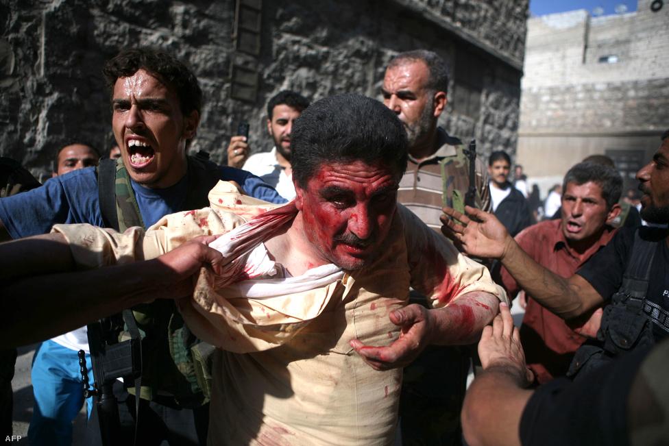 Afganisztán 2001-es, Irak 2003-as lerohanása és a 2011-es Arab tavasz utáni líbiai beavatkozás után a nyugati hatalmak nem akartak közvetlenül beavatkozni Szíriában, hogy egy újabb évekig tartó konfliktust vállaljanak fel. Ez pedig ahhoz vezetett, hogy egyre több lázadócsoport alakult az országban. A polgárháború alatt ezért egyre véresebb lett. A kormányhoz hű katonai csapatok helyett sokszor a rendőröket támadták meg a könnyű fegyveresek. A képen egy rendőrtisztet hurcolnak el az SZSZH fegyveresei. A 2012 júliusi aleppói rajtaütésben a megfigyelők szerint 40 rendfenntartót végeztek ki.