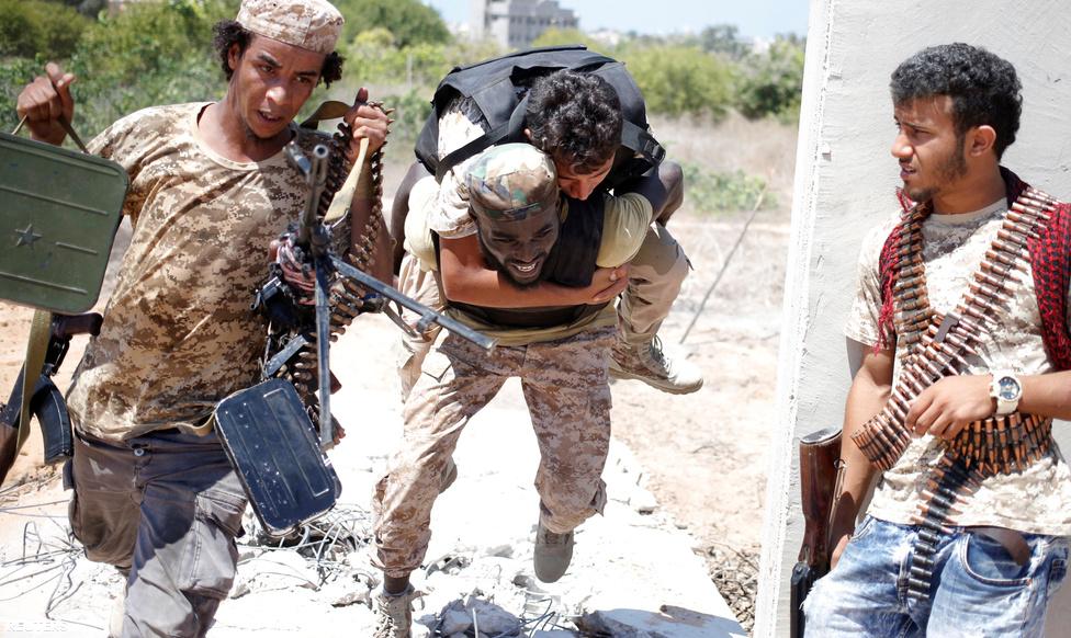 """Erre teljes joggal illik a """"drámai kép"""" jelző:  ezek a harcosok sebesült bajtársukat, géppuskájukat és géppuska-lőszerüket egyszerre próbálják meg kimenekíteni az iszlamisták kereszttüzéből."""