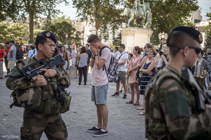 Gyászolók egyperces néma csenddel emlékeznek a nizzai terrortámadás áldozataira Párizsban 2016. július 18-án.