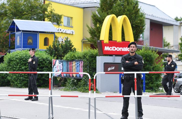 Rendőrök a müncheni olimpiai parkban található Olympia bevásárlóközpont mellett lévő gyorsétterem előtt 2016. július 23-án egy nappal az épületben történt lövöldözés után.