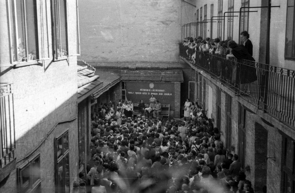 """A kép 1955-ben készült a Szentkirályi utca 12. udvarán. A tízes évek óta itt működő iparostanonc iskolát 1948-ban a Peterdy utcába helyezték és egy év múlva már a szovjet Pionír Palota mintájára úttörőműhelyek, könyvtár, olvasóterem, úttörőiskola, sport- és szakkörtermek várták Rákosi kispajtásait.Az úttörők aranyélete nem tartott sokáig, a hatvanas években ugyanis az Iskolai Felszereléseket Értékesítő Vállalat működött itt.Az úttörőmozgalom 1946-ban a Párt kezdeményezésére és vezetésével alakult, 1950-ben több mint 700.000 tagja volt. Boldog és vidám életükről Rákosi egész úttörőbirodalom keretében gondoskodott: volt színházuk, mozijuk, vasútjuk, stadionjuk, saját Úttörő Köztársaságuk Csillebércen. Az úttörőknek kötelessége volt, hogy a bukásra álló társaikat korrepetálják és rávegyék a tanulásra. De ez sem nekik, sem a tanároknak nem sikerült maradéktalanul, hiszen ideológiától átfűtött, iszonyatos mennyiségű és nem életkornak megfelelő tananyagról volt szó. A lemorzsolódás és a nagyarányú bukások a felszabadulás 10 éves évfordulójára is árnyékot vetettek. Talán éppen itt és most, a Pionír Palota fényével nem vetekedő józsefvárosi udvarban kapták meg az úttörők és vezetőik az eligazítást: """"Közoktatásunk nagy feladata, hogy az oktató- és nevelőmunka színvonalának emelésével dolgos, hazáját szerető, a béketábor nagy ügyéért lelkesedő, szocialista Magyarországot építő, öntudatos és képzett ifjúságot neveljen."""""""