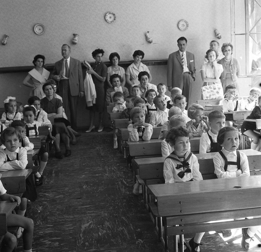 """Boldog szülők a Népművészeti Boltból származó kancsók és dísztányérok alatt. Elégedetten gondolnak a kék ívvel bekötött, vignettás füzetekre, az ÁPISZ-ban vásárolt töltőtollra, színes ceruzákra, iskolatáskára. De az állam azért ennél többet várt tőlük: azt, hogy zárjanak össze az iskola mögött és legyen összhangban az iskolai és az otthoni verzió """"a társadalomról, a jogokról és a kötelességekről, a világ eredetéről és fejlődéséről."""""""