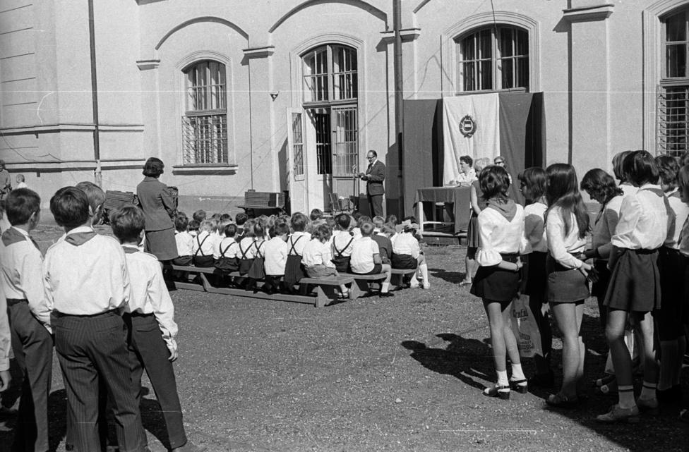 """Tanévnyitó a Medve utcai Általános Iskolában (ma Csik Ferenc Általános Iskola és Gimnázium). Fogadjunk egy nagycímletű iskolai takarékbélyegben, hogy a Németh László Úttörőraj jelen! Az író ugyanis idejárt elemibe, majd visszatért iskolaorvosként és egészségtan tanárként, 1937-ben pedig megírta """"A Medve utcai polgári"""" című könyvét. A fotón már tetten érhető a hetvenes évek laza szocialista eleganciája. Nejlon a zokni, az éltartó sötétkék fiúnadrág, a lányok szoknyája, az ing, a blúz. A zacskó. Holnap reggel előkerül az Úttörő Áruházban vásárolt nejlonköpeny is, fiúknak Peti és Matyi fazonban.  """"Könnyen kezelhető és sokáig szép marad."""""""