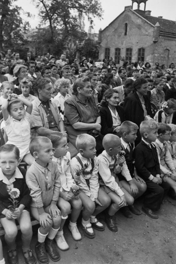 """""""Tanulóifjúságunk derűs, munkára, tanulásra kész serege"""" az első sorban.  Arcok, amelyekre Rákosi elvtárs varázsolt mosolyt. Övék a jövő, a sok-sok iskola, Sztálinváros és Inota. Legalábbis a korabeli Népszava szerint."""