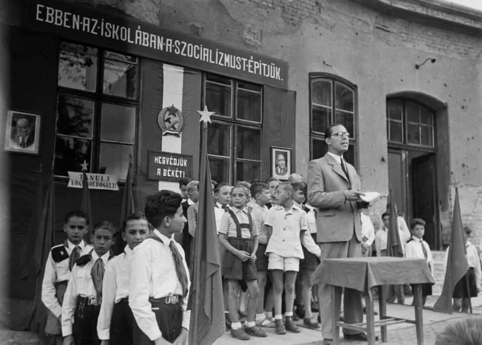 """1948 után minden valamirevaló iskola mozgalmár, hithű kommunista vagy pirosbetűs nap nevét viselte. A képen a XIV. kerületi Május 1. utcai (ma Liszt Ferenc) Általános Iskola udvara, a falakon háborús lövések, a levegőben félelem és reménytelenség. Az igazgató, államtitkár elvtárs vagy pártbizottsági másodtitkár Lenin és Rákosi éber tekintetétől övezve köszönti a tanévet. Sztálin jóságos mosolyának hiánya legalábbis szabotázs-gyanús. Bár tanévnyitó évekig nem múlhatott anélkül, hogy az agyakba és szívekbe ne karcolták volna a leckét: """"Szeressétek a Szovjetuniót, a nagy Sztálint, szeressétek Rákosi elvtársat, a magyar dolgozók gyermekeinek szeretett édesapját!"""" Utolérhetetlen előnnyel kezdte az iskolai évet a korszak diákja, hiszen """"boldog élete és szabad tanulása felett a magyar nép vezetője őrködött.""""  Esetleges cseréről (szabad élet, boldog tanulás) még sokáig nem lehetett szó. Az úttörőszettbe öltöztetett munkás-paraszt gyermekek láthatóan mit sem sejtenek kivételezett lehetőségeikről. A képen inkább unalomba, érdektelenségbe süllyedve, minden öntudat nélkül taposnak épp a volt uralkodó osztályok művelődési monopóliumán. A Párt és az egész dolgozó nép reménységei rezzenéstelenek maradnak a """"Megvédjük a békét!"""" és a """"Tanulj, hogy boldogulj!"""" jelszavakra is."""