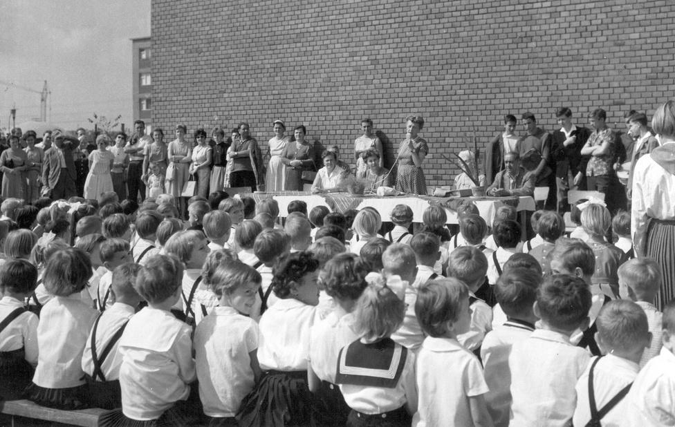 """Az Ifjúmunkás utcai iskola tanévnyitója 1968-ban az Üllői úti lakótelepen. Kádár az ablaktalan, égbe nyúló téglafallal üzent: a szocializmus építése nem állt meg az ötvenes években. Ugyanakkor a tanévnyitó soha nem hasonlított jobban egy táncdalfesztiválra: az igazgatónő úgy ragadja meg a mikrofont, mint aki a """"Jaj, tanár úr, kérem"""" után elénekli a """"Nem leszek a játékszered"""" c. slágert is. A falnak támaszkodó, fanyalgó arcú telepi vagányok témát gyűjtenek a következő levélhez, amelyet majd a szovjet levelezőpajtásnak írnak. A ma József Atilláról elnevezett lakótelep az egykori Mária Valéria nyomortelep helyén épült fel 1957 és 1965 között. A mintegy 90 hektárnyi területen több mint 30 ezer ember élt 1,5-2 szobás lakásokban. Bár építésekor a munkásság lakótelepének szánták, éppen annyira volt az, mint névadója a munkásság költője. Egy 1967-ben készült felmérés szerint elsősorban értelmiségiek és alkalmazottak éltek itt, meg majdnem ennyi betanított munkás, viszont szakmunkás alig. (Szűts Ildikó: Városi lakás, História 1986/5-6. szám)"""