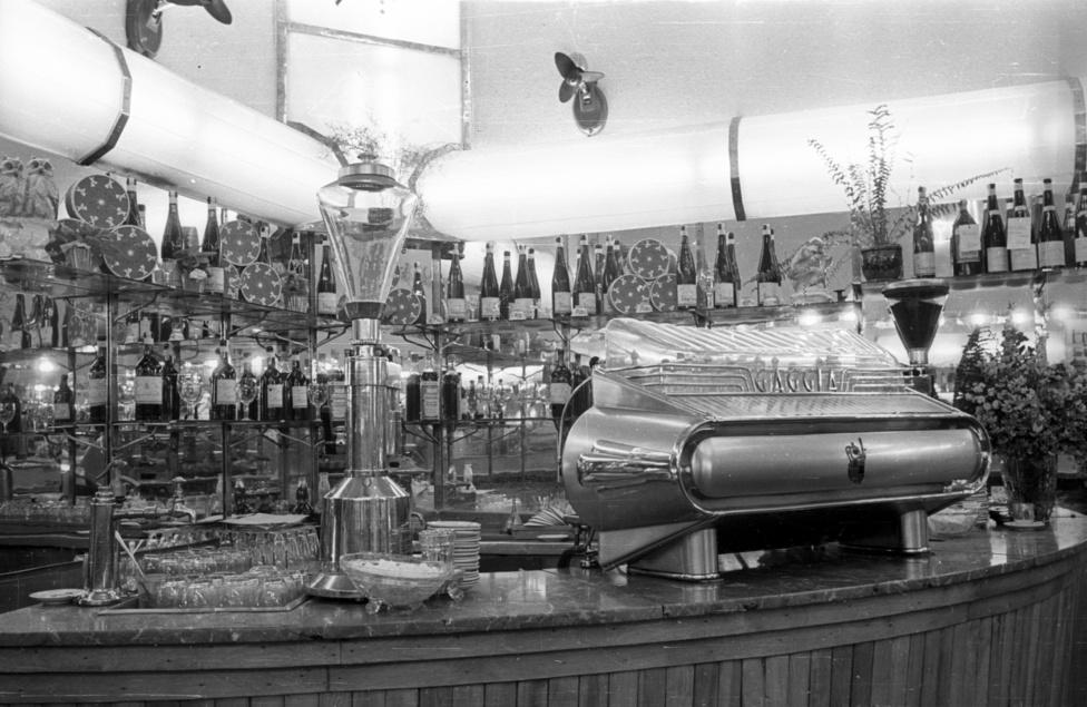 A képen az 1955 februárjában mgnyílt Kígyó utcai Mézes Mackó kávésarkát láthatjuk. A Mézes Mackók furcsa története szomorú véget ért, az alapító Onódy Lajost, és tizenegy társát a társadalmi tulajdont károsító bűncselekmények miatt 1964-ben börtönbüntetésre ítélték.Onódy egy roppant tehetséges káder volt, aki ügyesen feszegette a szocializmus határait, sikert sikerre halmozva. Még 30 éves sem volt, amikor 1949-ben megkapta az összes államosított büfét és eszpresszót, később pedig olyan híres szórakozóhelyeket is, mint a margitszigeti Casinó, a ferihegyi tranzit étterme, a Savoy, Abbázia, vagy a Váci utcai Anna Presszó.Munkája során rengeteg újítást vezetett be, az április 4.-i és május 1.-i felvonulásokra mozgó büfékocsikat küldött, olyan új gépeket hozott be külföldről, amik addig ismeretlenek voltak Magyarországon, a csavaros fagyit adó lágyfagylalt-gépeket, a krumplisütéshez használt fritőzt, de a zenegépeket is neki köszönhetjük.1955-ben új koncepció alapján nyitott meg az első Mézes Mackó, a cukrásztermékek mellett fantasztikus hidegkonyhájával tarolta le a piacot, több mint 80 féle termékkel. A franciasaláták, aszpikos sonkatekercsek, kaszinótojások és majonézes termékek ilyen választékával addig sehol nem találkozhatott a budapesti lakosság, így nem csoda hogy a kezdeti napi 5000 forintos forgalmat pár hónap alatt megháromszorozták. Fél évvel a nyitás után is általános volt a 30-35 perces sorbanállás, a Népszava javasolta is a névváltást Szardíniás Dobozra.A sikeren felbuzdulva sorra nyitottak a fővárosban az újabb Mézes Mackók, sőt hamisították is őket, simán Mackó néven is nyitottak üzletet vidéken, de a korai franchise-rendszert másolták le a Lucullus, Pingvin és Kávés Katica-láncok is.Onódy kényes volt a berendezésre és a gépparkra, szerencsére jó politikai kapcsolatai révén beszerezhette az olasz Gaggia kávégépek legújabb típusait, a Kígyó utcai Mackóban ez az 1952-es háromkaros csúcsmodell csöpögtette a krémkávét.Azonban a politika már a hatvanas évekbe