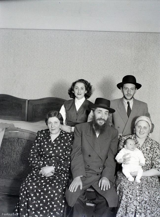 """Családi otthon, valahol Erzsébetvárosban. Ezen a környéken nagyszámú ortodox zsidóság élt, hogy a szombatokon gond nélkül eljuthassanak a zsinagógába járművel való utazás vagy túl sok gyaloglás nélkül is. A fotón az idősebb asszonyokon paróka, kendő. A hajadon lány saját hajjal és fedetlen fejjel is mutatkozhatott, amíg férjhez nem ment.A legnehezebb helyzetbe pont ők, a vallási hagyományaikat megtartani akaró ortodox zsidók kerültek. Azzal, hogy a Rákosi-korszakban bevezették a szombati munkanapot, miközben az egyéni iparengedélyeket bevonták és a kisipart, kiskereskedelmet ellehetetlenítették – választásra kényszerítették őket megélhetés és vallás között. Megoldást csak a szombattartó szövetkezetek jelenthettek (itt a korábbi kisiparosok és –kereskedők kaphattak munkát és a szombati nap hallgatólagosan nem volt munkanap).A lakáskérdés egyébként a háború utáni élet egyik nagy problémája volt. A kibombázottak, menekültek, visszatértek elhelyezése sok gondot okozott. A Haladás így írt erről 1948-ban: """"Ha a deportált lakását kényszerű távolléte alatt másnak utalták ki, vagy akár önhatalmúlag foglalta el valaki, akkor a hazatérő zsidónak egy szobát vissza kell kapnia. Kivétel az az eset, ha a lakás csak egy szobából áll. Ebben az esetben a deportált hazatérő nem kapja vissza a lakását."""""""