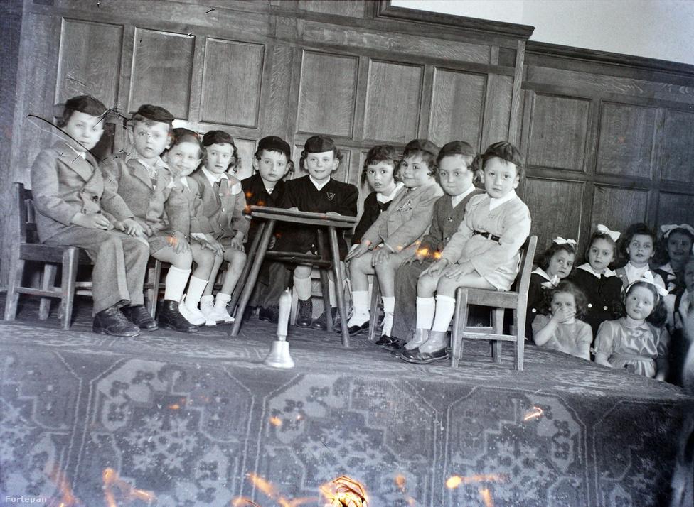 """Ismét óvodások a színpadon, de a helyszín most a hitközség díszterme a Dob utca 35-ben. A Budapesti Autonóm Orthodox Hitközség """"kétéves küzdelem után jöhetett létre a neológia aktív ellenállása ellenében. A küzdelmek hevességét jelzi, hogy az országgyűlésben Deák Ferenc és Jókai Mór hívta fel a figyelmet arra, hogy a lelkiismereti es vallásszabadság a zsidó vallás tradícióit őrző közösségeknek is jár, különösen, ha azok a zsidóság többségét is alkotják. 1871. november 15-én jelent meg az a rendelet, amely törvényesen lehetővé tette, hogy a zsidó orthodoxia létrehozza a maga szervezetét"""" - írja Dombi Gábor.A hitközség ma is álló épületét és a zsinagógát a Löffler-fivérek tervezték az 1910-es években. A Kazinczy utca felől sikátoron keresztül megközelíthető épületben kapott helyet az elemi és a polgári iskola egy része, udvarán ma is ott áll a Hámori Gyula esküvői fotóin is sokszor felbukkanó hüpe (esküvői sátor)."""