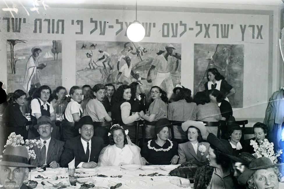"""Ortodox zsidó esküvő, a helyszín ismeretlen. A lakodalmi ebéd szigorú rend szerint zajlott, külön asztalnál étkeztek a nők és a férfiak. Eredetileg koldusasztalt is állítottak, ahol a környék szegényeit vendégelték meg - ez a háború utáni korszakban nyilván elvesztette jelentőségét. Az ortodox zsidóság számára a kóser étkezés alapokig meghatározó volt, visszaemlékezések szerint akár a munkaszolgálatos behívóra adott zsigeri válasz is lehetett a """"de mi lesz a koszttal?""""."""