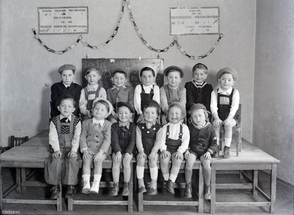 """A Hanna Gyermekmenza és Napköziotthon óvódásai a Kertész utca 32-ben. A """"Hanna"""" fogalom volt a pesti ortodox zsidóság körében, mióta 1921-ben a tizenkilenc éves Heiden Dóra (1903-1963) megalapította – átvéve a Magyarországot több év után elhagyó nemzetközi segélyszervezetek feladatait az átrajzolt határok miatt Budapestre menekült zsidó szegénygyerekek ügyében. Heiden Dóra 1927-ben férjhez ment egy rabbihoz és Amerikába költözött, de az általa létrehozott szervezet folytatta a munkát. A harmincas-negyvenes években elsősorban az ortodox hitközség nyilvános iskoláiba járó szegénygyermekek napközi gondozását, étkeztetését (rituális étkeztetés, saját konyháján), felruházását és nyaraltatását végezték. Az iskolai tanévben a Kertész utcában működött 100 körüli létszámmal, nyáron Nagymaroson, Zebegényben táboroztattak. Fenntartója a Hitközség és magánadományozók voltak, de évekig támogatója volt kisebb összegekkel a Fővárosi Közgyűlés is."""