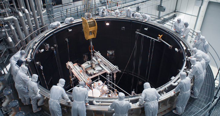 A szondát ellenőrző kutatók és mérnökök várakoznak a vákuum-kamra körül