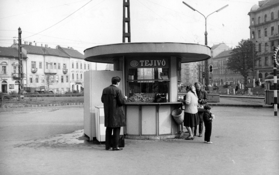 Ezen a 68-as képen megint egy olyan okból áll egy pavilon, melyre korábban nem volt megoldás, mert nem nagyon létezett. Egy tejivó, vagyis amolyan reggelizőhely. A kirakatában halomban állnak a kiflik.