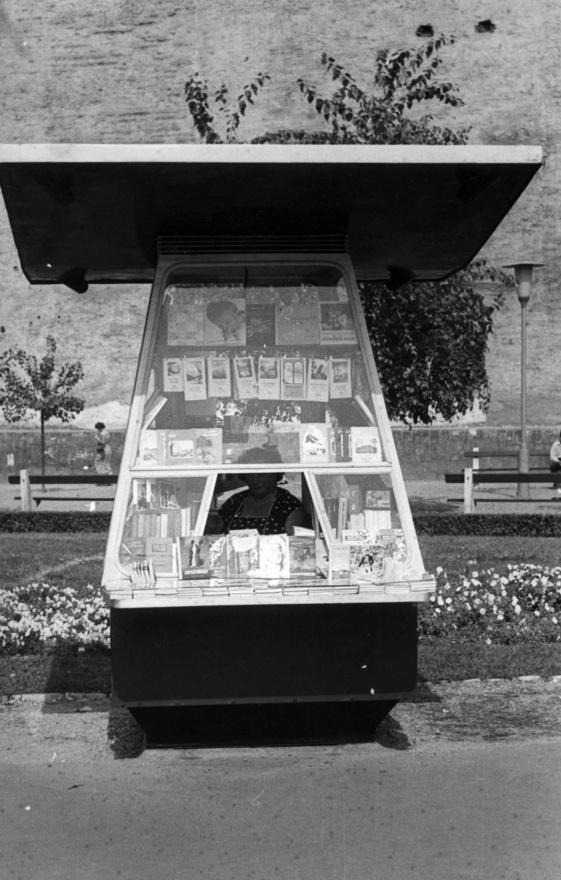 A könyv a XX. század második felében vált igazán tömegcikké, a keleti blokkban pedig kifejezetten fontos volt. Egyrészt mint ideológiaközvetítő, másrészt mint szimbólum: a munkásosztály felemelkedésének egyik jele volt, hogy mindenki olvas. Hirtelen szükség lett egy csomó könyvesboltra, amit a hagyományos kereskedői hálózat nem tudott kiszolgálni. Főleg a lakótelepen kellettek különféle pavilonok, mert ott a házak aljában (még) nem voltak boltok, a központi áruházak pedig nem tudtak minden igényt kielégíteni.Persze ne legyünk igazságtalanok, az utcai könyvárusítás nem csak a szocializmushoz kötődik: épp a rendszer váltás után, a kilencvenes években volt egy hatalmas fellendülése a mobil standoknak. Akkoriban minden metrófeljáróban volt két-három ilyen könyves pult, melyeket aztán a kiépülő új boltláncok (meg a szigorúbb szabályozás) szorított ki.
