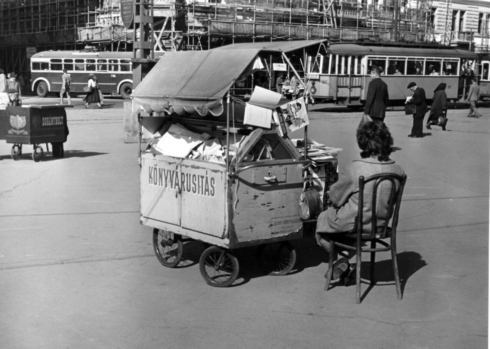Bár ennek a Baross téren álló kiskocsinak az oldalán az Állami Könyvterjesztő Vállalat felirat szerepel, talán itt sem egy tömegtermékről van szó. Lehet, hogy a kerekei egykor egy babakocsin forogtak, s talán a ponyva sem itt kezdte pályafutását. Hogy a kép készültekor, 1958-ban mennyire népszerű volt ez a műfaj, jól mutatja, hogy pár méterre tőle egy dohányárus kocsija áll.
