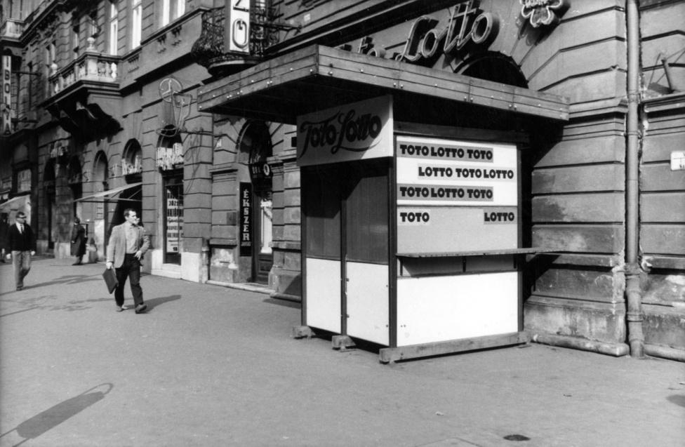 Ez az 1964-es fotó tökéletesen ábrázolja, hogyan állt az akkori vezetés a városkép védelméhez. Egy már újkorában is igénytelen, ideiglenes anyagokból összetákolt, gerendákra állított lottózóbódét állítottak, egy már meglevő lottózó elé. Hogy mi szükség volt erre, azt csak tippelgetni lehet. Ha nem találkoznánk még ma is hasonló építményekkel a pesti utcákon, azt mondanám, biztos csak felújították a mögötte levő üzletet. A tipográfiai kuszaságról – egy négyzetméteren belül háromféle totó-lottó felirat – most ne is beszéljünk.