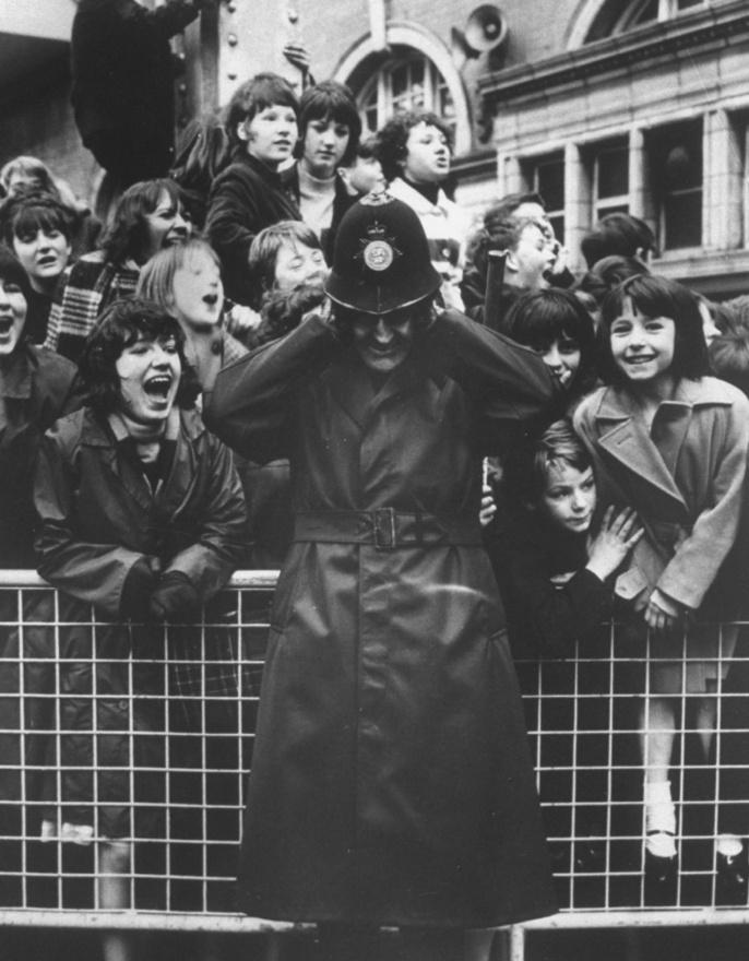 Nem csoda, hogy szegény rendőr befogja a fülét, hiszen a bezsongott tinilányok még a koncerteken is mindent elnyomtak a sikoltozásukkal. Az akkori kezdetleges hangtechnika még nem tudott segíteni ezen a problémán, sokszor sem Lennonék nem hallották magukat rendesen, sem pedig a közönség. Jellemző, hogy a Beatles 1965-ös, Shea Stadium-beli történelmi jelentőségű koncertjéről (ez volt ugyanis az első igazi stadionkoncert) készült filmfelvételen sem hallatszik szinte semmi az ötvenezer sikoltozó néző miatt, ezért később a zenekar egy stúdióban újra fel kellett, hogy játsszon néhány dalt a koncertfilmhez.
