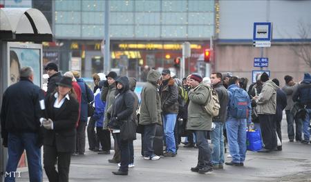 utasok várakoznak a buszmegállóban