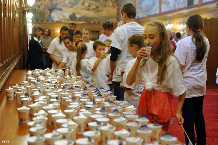 A meghívott gyerekek iskolatejet isznak az Országház Vadásztermében az iskolatej világnapja alkalmából rendezett ünnepség végén.