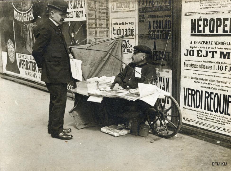 Népopera és Requiem, a háttérben megbúvó sátánnal: kerékpárra szerelt újságárussátor a budapesti utcán 1916-ban. Ebben az évben mutatták be a Csárdáskirálynőt és a Mágnás Miskát is. A visszaemlékezések szerint amolyan haláltánc-hangulat uralkodott el a városon, mintha mindenki még egy utolsót, egy nagyot szeretett volna mulatni, megfeledkezve a háborús hírekről. Az árus bizonyára egyike a hadirokkantaknak.