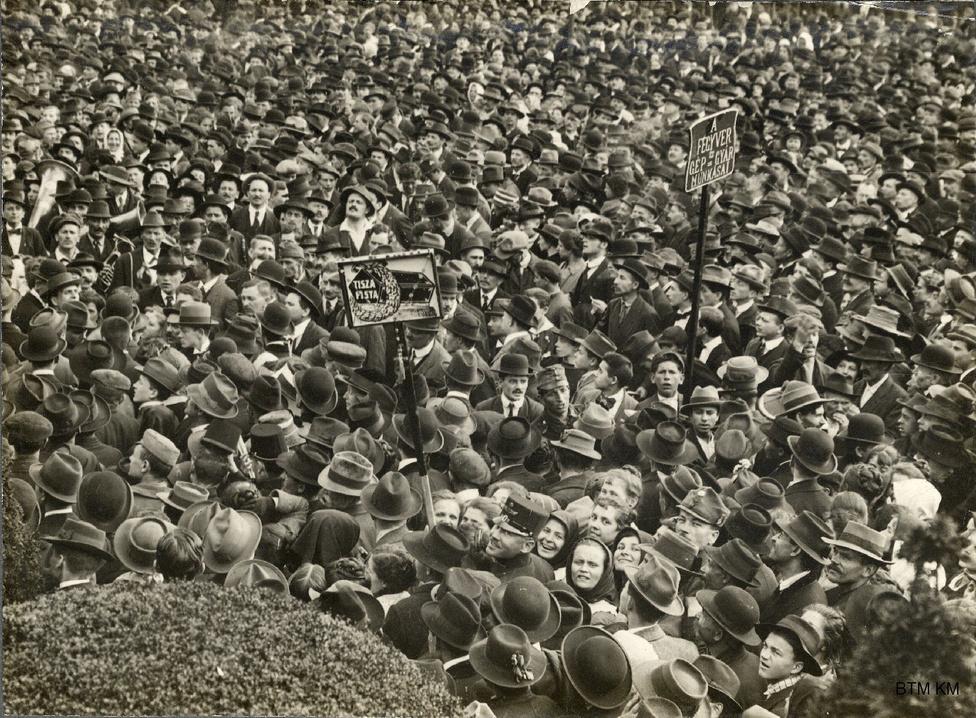 """Tömegtüntetés a békéért és az általános és titkos választójogért, 1917 tavasza vagy nyara. A """"Tisza Pista"""" feliratú koporsó tábláját egy mosolygó katona tartja. Az egyre inkább megcsömörlő közvélemény szemében a hadbalépést eleinte határozottan ellenző Tisza lett a háború elsőszámú bűnbakja. Őt 1917 májusában sikerült végül lemondatni. Az osztrák miniszterelnökkel ekkorra már merénylet végzett, de Tisza sem kerülhette el a sorsát: a negyedik, ellene elkövetett merényletben 1918. október 31-én gyilkolták meg."""