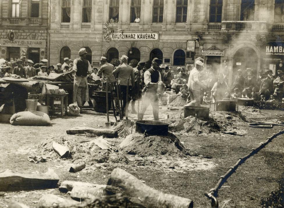 """Tábori konyha a Népopera mögött a Tisza Kálmán téren, a fotón kivehető a fényképész pecsétje. Müllner sokszor több helyre is eladta ugyanazokat a képeket. A háború konjunktúrát hozott neki, a lapokon kívül más intézmények is megvették a felvételeit. Egyik állandó vevője a Fővárosi Múzeum (a Kiscelli elődje) volt, mely fővárosi tanácsi határozat alapján lényegében az utókor számára végzett gyűjtőmunkát ekkor: átfogóan gyűjtötték a """"nagy háborúra"""" vonatkozó emlékeket a röplapoktól az albumokig."""