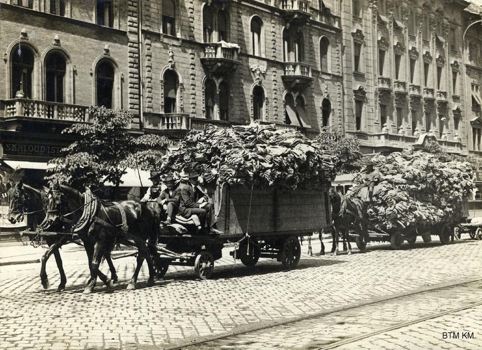 """Ruhaszállítás a katonák részére a József körúton 1914-ben. """"Hadvezetőségünk azzal a kéréssel fordul a magyar nőkhöz, hogy a csatában küzdő katonáinknak magasztos feladataik teljesítésében segítő kézzel támogatására legyenek és könnyítsék meg katonáinknak az északi hideg klíma könnyebb elviselését úgy, hogy mindegyikük, amennyire az anyagi tehetsége és ideje megengedi, kézvédőket és hósapkákat készítsen."""" A Pesti Hírlapban megjelent közleményhez számtalan hasonló született az első hetektől fogva. Az udvari ellátmány nem csak hiányos volt, a szín sem stimmelt: a csukaszürke uniformis nem álcázott jól, nem beszélve a huszárok hagyományos piros-kék egyenruhájáról."""