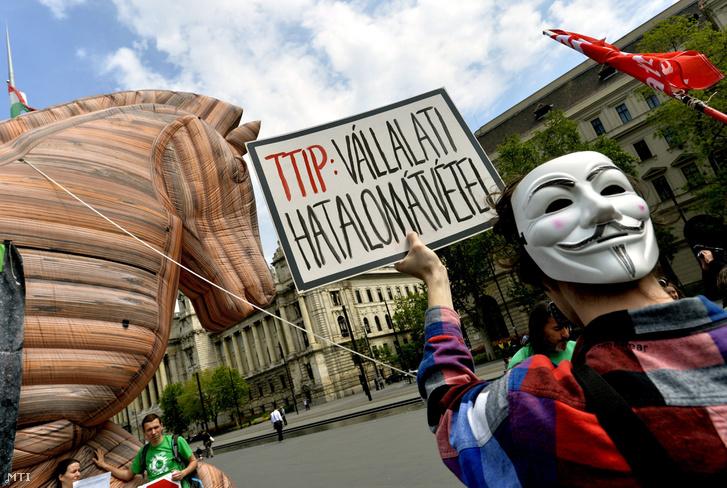 A több mint négyszáz éve kivégzett angol katolikus lázadó Guy Fawkes maszkját viselő aktivista az Európai Unió és az Egyesült Államok közötti szabadkereskedelmi egyezmény a Transzatlanti Kereskedelmi és Beruházási Partnerség (Transatlantic Trade and Investment Partnership TTIP) ellen tiltakozásul felállított nyolc méter magas felfújható trójai falónál amelyet a Föld Barátai Európa nemzetközi akciósorozata keretében a Magyar Természetvédők Szövetsége és a Közép-magyarországi Zöld Kör állított az Országház előtti Kossuth Lajos téren 2016. május 5-én.