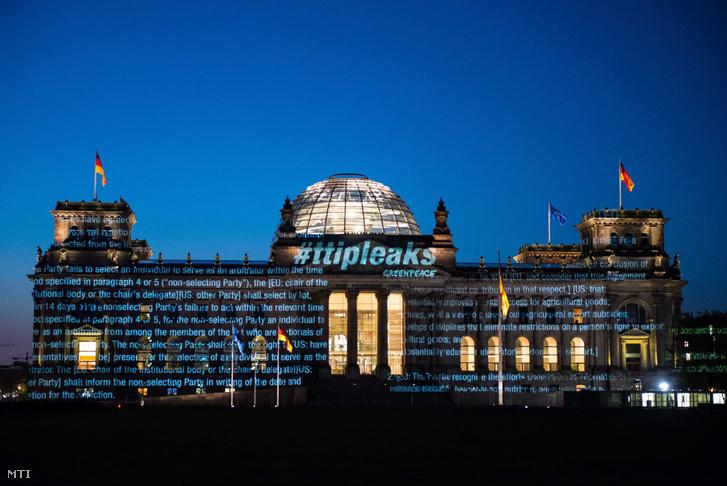 A Greenpeace környezet- és természetvédelmi civil szervezet által közreadott képen a szervezet aktivistái egy titkos megállapodás kivonatát vetítik a német törvényhozás épületének a berlini Reichstagnak a homlokzatára 2016. május 2-án hajnalban.