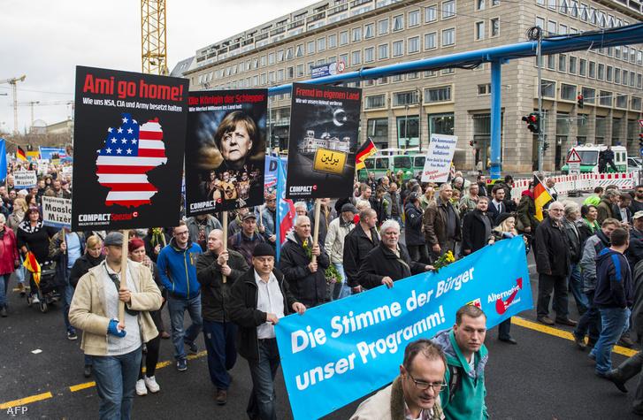 AFD-párti tüntetők Nyugat-és Merkelellenes plakátokkal tüntetnek egy 2015. novemberi demonstráción