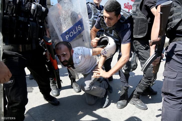 Rohamrendőrök vesznek őrizetbe egy tüntetőt a tömeges felfüggesztés ellen szervezett tiltakozáson, Diyarbakir városban, 2016. szeptember 9-én.