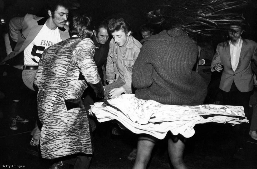 A kép a hackney-i Adam and Eve pubban készült 1976-ban, és már jól látszik, milyen változásokon ment át a mozgalom két évtized alatt: a zakók hossza és színe már eltér, megjelentek a színes Edward korabeli zakók, a hosszú barkók, és már a vadabb frizurát is a kreativitásnak több teret engedő hajlakkal lövik be, nem pedig sima brillantinnal. Sőt, feltűntek a fekete teddy boyok is – nem túl sokan, de az ilyesmi az ötvenes években még elképzelhetetlen volt.
