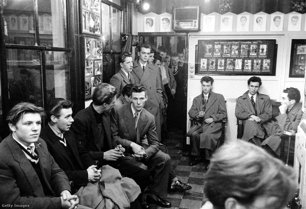 """Fiatalok várakoznak a fodrásznál Hounslow-ban (1953). Bár a teddy boy kifejezés először 1953 októberében jelent meg a Daily Mirrorban, a londoni újságok már két évvel azelőtt is cikkeztek bandákba tömörült, elegánsan öltöző fiatalokról, akik nemcsak fiatalabbak, de erőszakosabbak is voltak a spiveknél. Eleinte """"cosh boy""""-ként (kb. ólmosbotos fiúk) emlegették őket, de később az Edwardian lett az állandó jelző, és ebből lett a teddy boy."""
