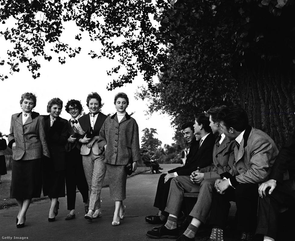 """Az ötvenes évek közepére a teddy boy jelenség már országos lett, és az egymástól élesen elkülönülő brit társadalmi osztályok miatt ez azzal is járt, hogy a középosztályban és attól felfelé ciki lett az Edward korabeli divat, miután azt a lenézett alsóbb néposztályok kisajátították maguknak. Ez a kép 1955-ben készült egy dél-londoni parkban, amikor már a teddy boy egyet jelentett a közvélemény szemében a huligánnal, és számos szórakozóhely bejáratánál ott volt a ma abszurdnak ható """"no Edwardian dress"""" felirat."""