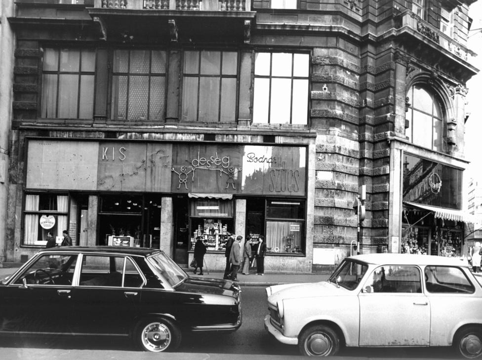56 sokkja és a következő évek megtorlásai után a Kádár-rendszer 1963-tól konszolidálódni kezdett, ami magával hozta azt is, hogy a rendszer egyre inkább szerette volna boldogan fogyasztani látni alattvalóit. Az áruhiány enyhülni kezdett,  az állam  az Új Gazdasági Mechanizmus részeként pedig azon dolgozott, hogy a lehetőségek között mindenki az igénei szerint tudjon vásárolni. Ez, ahogy Valuch Tibor történész magyarázza, a fogyasztás és vásárlás tereinek differenciálódásához vezetett. Kialakulatak a vásárlás különböző övezetei, amelyekben az egyszerű proletártól a szocialista középosztályig mindenki megtalálhatta a saját vásárlóterét.