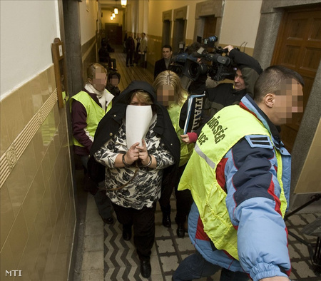 Rendőrök bilincsben vezetik el Sz-né Sz. Eleonórát a Pesti Központi Kerületi Bíróságon tartott tárgyalásról (Fotó: Szigetváry Zsolt/MTI)
