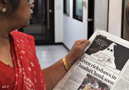 """Egy indiai nő szemléli a Mail Today napilapban január 5-én megjelent karikatúrát, ami a Ku-Klux-Klan csuklyájába öltözött figuraként mutatja be az ausztrál rendőrséget. """"Azon vagyunk, hogy feltárjuk a bűncselekmény indítékát"""" - mondja a fehér felsőbbrendűséget hirdető arctalan karakter (Fotó: Raveendran/AFP)"""