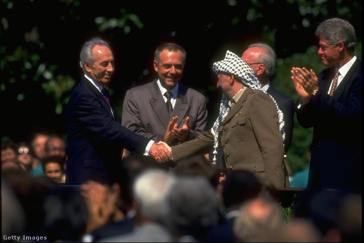 Arafat és Peresz fogank kezet az Oslói megállapodás aláírása után 1993. szeptember 13-án a Fehér Házban. Mellettük Adrej Kozirjev orosz külügyminiszter, Jichák Rabín izraeli miniszterlnök és Bill Clinton amerikai elnök.