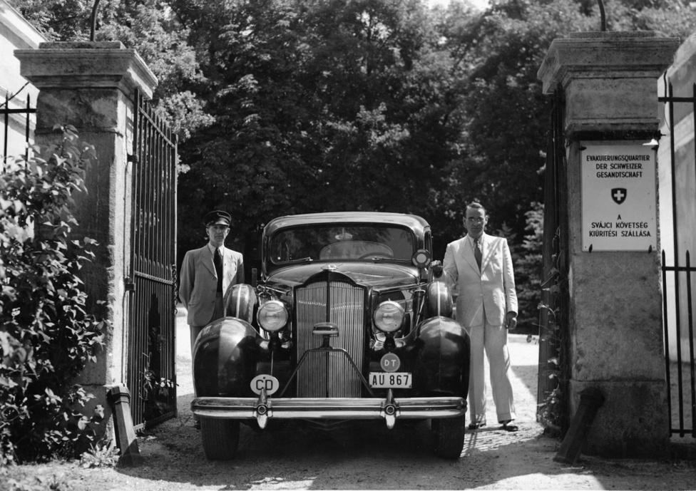 """Carl Lutz a bicskei hegyikastély bejáratánál kocsijával és sofőrjével 1944 nyarán. A bicskei hegyikastélyt Batthyányi Kázmér építette magyartanárának, teljhatalmú intézőjének, Nagy Károly csillagásznak, akinek csillagászati kutatásait is finanszírozta.  Az épület a XX. század első felében a Stéger család tulajdonába került, ők ajánlották fel a svájci követségnek, azt remélve hogy a követség védelme alatt átvészelhetik az 1944-es évet. A család sorsát nem tudtam felderíteni, az azonban biztos, hogy Carl Lutz Edmund Veesenmayer német teljhatalmú megbízottnál, valamint Adolf Eichmannál is eljárt a család kiszabadítása érdekében.1944 december végétől 1945 január végéig a kastély a német és szovjet csapatok között többször is gazdát cserélt. Birtoklásáért különösen elkeseredett harcok folytak, miután az """"Wiking"""" 5. SS-páncéloshadosztály Fritz Dargesáltal vezetett harccsoportja január 5-én visszafoglalta a kastélyt. Darges ezért a tettéért 1945. április 5-én a Vaskereszt Lovagkeresztje kitüntetésben részesült. A harcok során a kastély szinte teljesen megsemmisült, a mellette épült csillagvizsgáló és mauzóleum is súlyos sérüléseket szenvedett."""