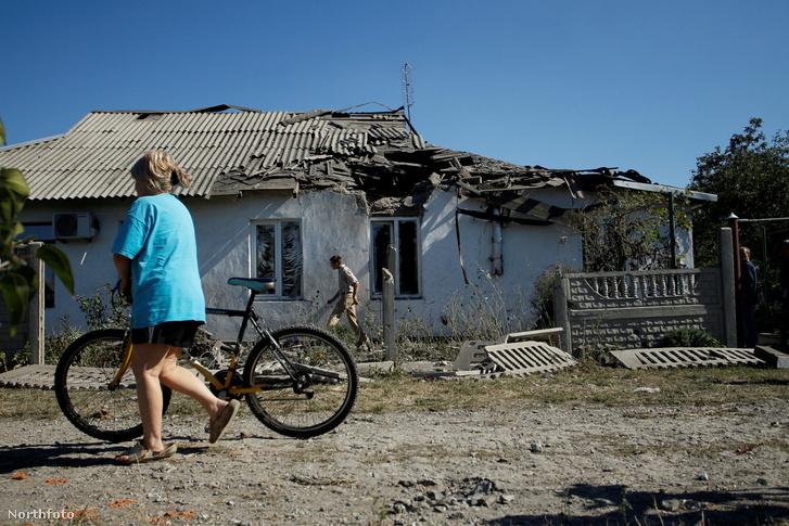 Lebombázott házak között sétálnak a helyiek egy donyecki faluban szeptember 14-én.