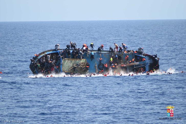 Az olasz haditengerészet által közreadott felvételen menekültek ugrálnak a tengerbe egy süllyedő hajó fedélzetéről Líbia partjainál 2016. május 25-én.