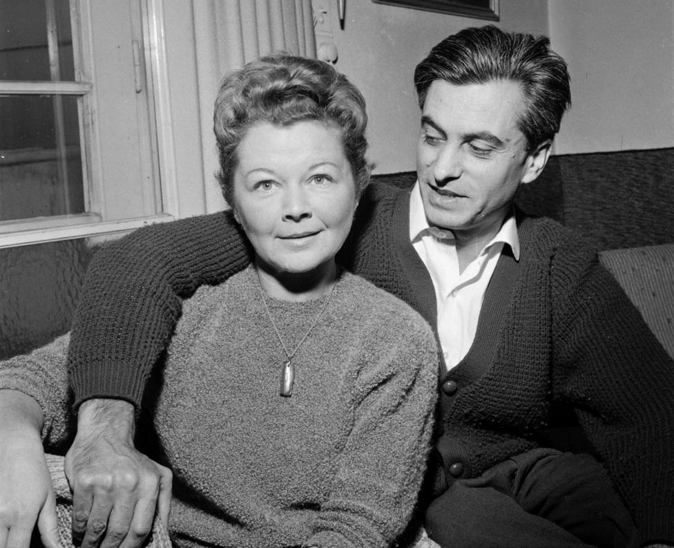 """Rab Zsuzsa (1926-1998) és Csanádi Imre (1920-1991) a Lóczy Lajos utca 5-ben. A lakásban eredetileg az író, költő, műfordító, újságíró Rab élt első férjével, a Vackor-könyveket jegyző Kormos Istvánnal (1923–1977), aki pár év után a túlságosan rendezett körülmények (koloniálbútorok, több rend ruha és cipő) elől 1963-ban Franciaországba és egy új szerelembe menekült. Párizsból viszont áldását küldte az új frigyre, sőt ki tudja, miért, ahol csak lehetett, igyekezett a volt feleség és az új férj fordításait, verseit elhelyezni. """"Akinek tíz nagy verse van, az nagy költő, és Csanádinak van tíz nagy verse"""" – mondta. Akinek van kedve, olvasson utána."""