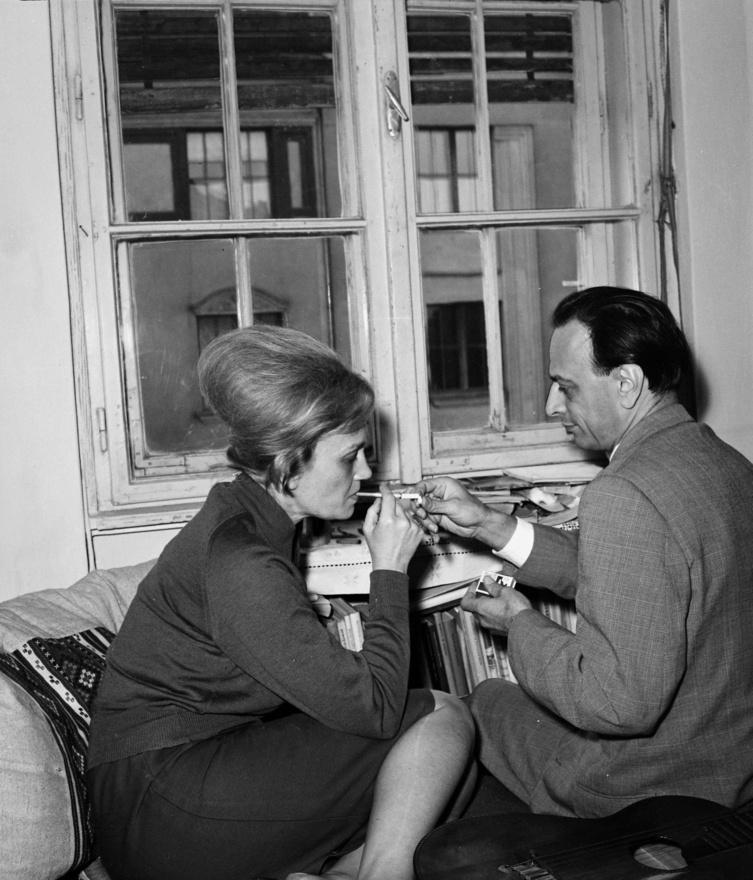 """Nemes Nagy Ágnes (1922-1992) és Lengyel Balázs (1918-2007) a Királyhágó utca 2-ben. A házaspár 1958-ban elvált, a költőnő ekkor költözött a lakásba, férje pedig pár házzal odébb. Sosem szakadtak el egymástól. Évtizedekkel később, amikor már mindketten idősek és betegek voltak, Lengyel második felesége, Vera kísérte át férjét és egy presszóban várakozott, míg az egykori pár irodalomról beszélgetett.                         Nemes Nagy Ágnes, a szép magyar–latin–művészettörténet szakos egyetemista és Lengyel Balázs, az ellenzéki mozgalmakkal kapcsolatot tartó jogász 1942-ben ismerkedett meg egy diákkori barátnő révén. Igazi háborús esküvő volt az övék 1944-ben. Lengyel Balázs közben elhagyta alakulatát, Budapesten bujkált katonaszökevényként és Nemes Nagy Ágnessel együtt több embert megmentettek (ezért 1997-ben megkapták """"Yad Vashem"""" kitüntetést Izraeltől).                         A pamlagon hever a költőnő gitárja. Lator László visszaemlékezése  szerint Nemes Nagy Ágnes szeretett énekelni: zsoltárokat és a 20-as évek kupléit, slágereit."""