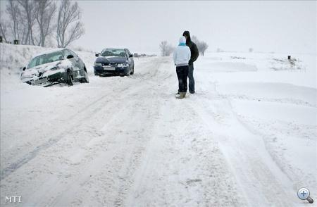 Árokba csúszott személygépkocsi mellett várakozik egy férfi és egy nő a Nagykanizsát Szepetnekkel összekötő úton.