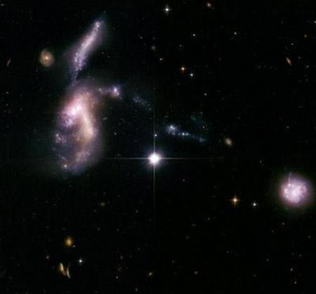 Az összeolvadó galaxishalmaz részlete. Jól megfigyelhetők az árapályerők által eltorzított alakú törpegalaxisok, melyekben a fényes területek intenzív csillagkeletkezési tartományokat jeleznek