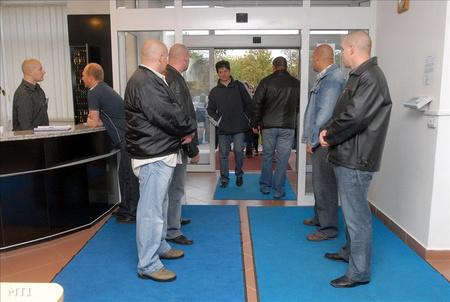 Biztonsági emberek sorfala között érkeznek a munkásgyűlésre a dolgozók a Pécsi Vízmű Zrt. székházába tavaly októberben