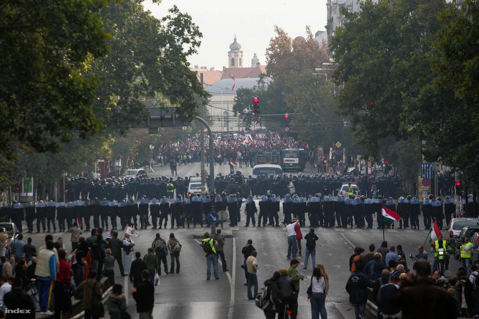 """A forradalom ötvenedik évfordulójának délelőttjén kisebb tüntető csoportok bolyongtak Pest különböző részein: százas csoportok demonstráltak a Kossuth tér körül, a Bazilikánál, a Szabadság térnél, az Arany János utcánál. Az ideológiai káoszt jelzi, hogy miközben egyesek a kormány lemondását követelték, az Index tudósítói beszámoltak olyan csoportról, amelyik azt kántálta a rendőrök felé, hogy """"Olaszliszka, Olaszliszka"""", amelynek kevés köze van a politikához, több a cigányellenességhez. Mindeközben a szélsőjobbos Hegedűs Lóránt a drámai hangulat fokozása végett félreverte a harangokat templomában."""
