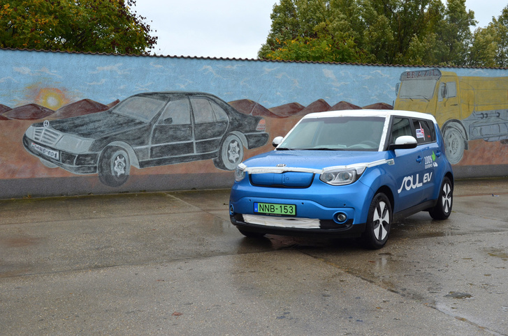 Az zavarosan olajos múlt és a feszültséggel teli jövő egyetlen képen: az olajszőkítők járműparkját megörökítő naiv művész falfestménye előtt a tisztán elektromos hajtású Kia Soul EV