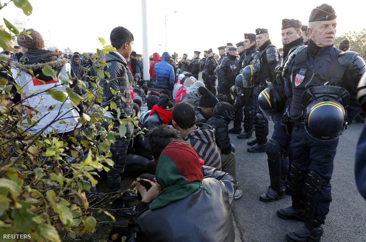 Francia rendőrök vigyáznak a buszra váró menekültekre a tábor kiürítése közben.