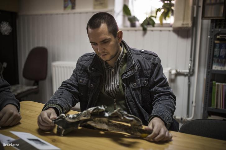 """Sándor Máté, a Dráva Múzeum munkatársa mutatja meg a bombakazetta náluk őrzött darabját. """"Négy évvel a bombázás után adományozta a múzeum volt munkatársának apósa - meséli, hogyan került a relikvia a múzeum tulajdonába. – A nagyobb darabokat a hatóságok elvitték, a többit, így ezt is, a lakosok tették el."""""""